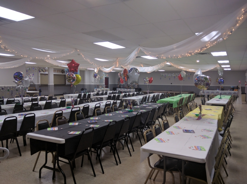 Photo of the hall prepared for an adult's birthday party. Note the bar (shown closed) to the left, for which beer, wine, and liquor and our bartender can be made available, if desired. To the back of the photo is the stage.